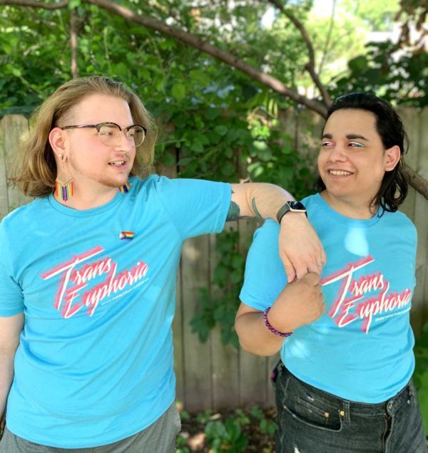 "Two trans people, one white with long blond hair and rainbow dangle earrings, and one Latinx with light brown skin, long dark brown hair and trans-flag-colored eye shadow. They look at each other, smiling and holding hands. They both wear bright blue t-shirts that say ""Trans Euphoria."""