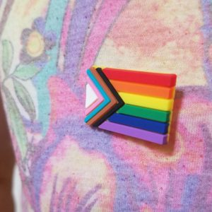 A progress pride lapel pin on a lightly floral shirt.
