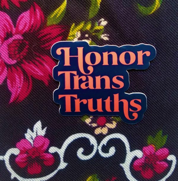 Set against a rich dark floral cloth, sits a dark blue vinyl sticker that say Honor Trans Truths in an deep coral embellished font.