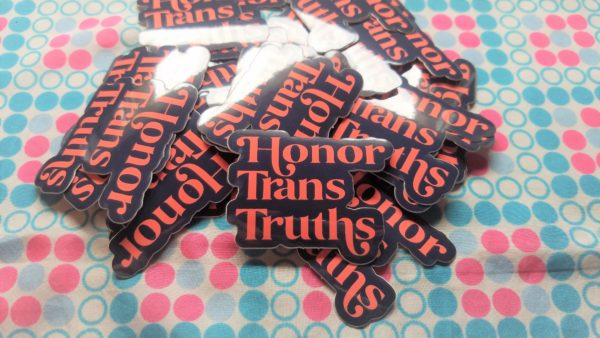 Set against a bubbly pink white and blue fabric, sits a stack of dark blue vinyl stickers that say Honor Trans Truths in an deep coral embellished font.
