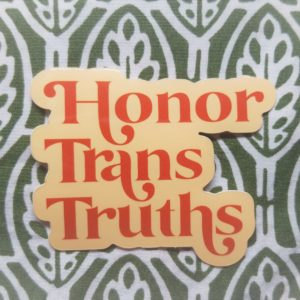 Set against a dark green and white design sits a cream colored vinyl sticker that says Honor Trans Truths in an burnt orange embellished font.