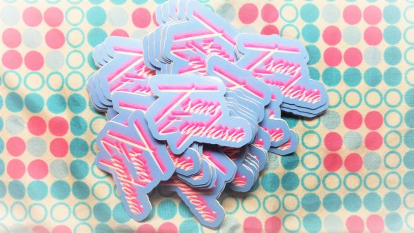 Set against a bubbly pink white and blue fabric, sits a stack of light blue vinyl stickers that say Trans Euphoria in bright white scrawling text with a bright pink shadow.
