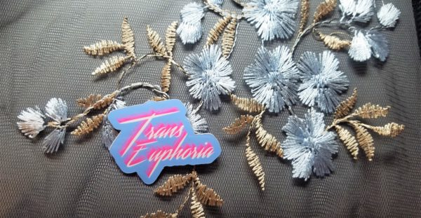 Set against a black mesh fabric with shimmery gold and silver embroidered flowers, sits a light blue vinyl sticker that says Trans Euphoria in bright white scrawling text with a bright pink shadow.